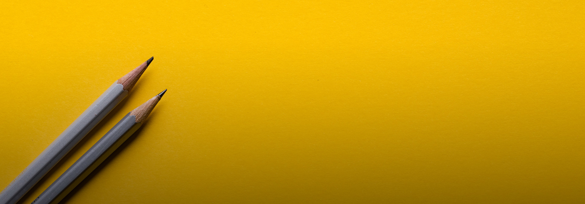Two pencils laid on a yellow background.