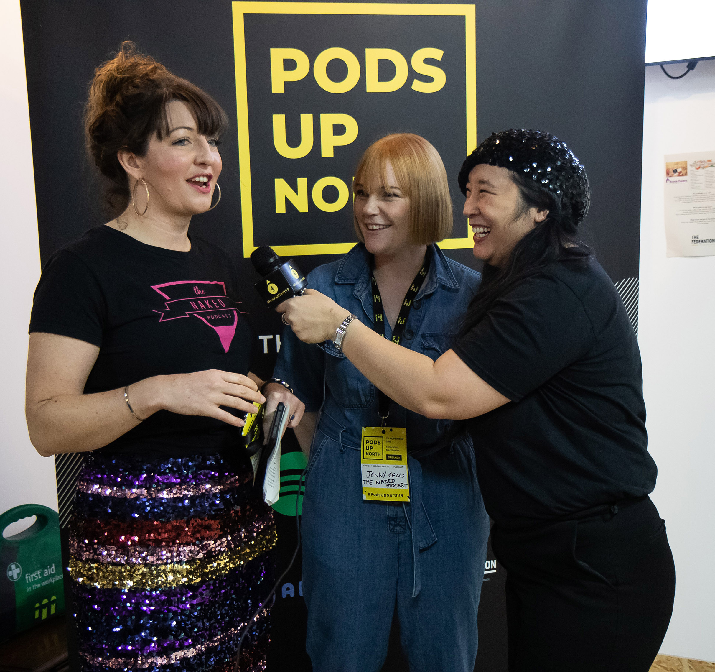 a photo of 3 women. one is wearing a hat and holding a microphone up to the mouth of one of the women as if to interview her